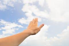 Παλάμη χεριών στο μπλε ουρανό με τα σύννεφα στοκ φωτογραφίες