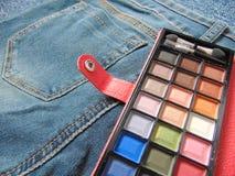 Παλέτα ταξιδιού τσεπών makeup στα τζιν Στοκ Φωτογραφία