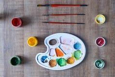 Παλέτα χρωμάτων με τις βούρτσες στην ξύλινη επιτραπέζια κορυφή Στοκ Εικόνες