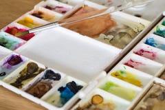 Παλέτα χρώματος πλαστικών καλλιτεχνών στην ξύλινη έννοια τέχνης πατωμάτων Στοκ φωτογραφία με δικαίωμα ελεύθερης χρήσης