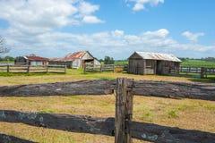 Παλαιά αγροτικά υπόστεγα πέρα από τους φράκτες θέσεων και ραγών στην αγροτική αγροτική σκηνή Στοκ Εικόνες