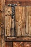 Παλαιά αγροτική πόρτα ξύλου πεύκων με τον επεξεργασμένο σίδηρο γεια Στοκ Φωτογραφίες