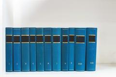 Παλαιά αναδρομικά βιβλία με τις καλύψεις χρώματος σε μια άσπρη μπροστινή άποψη ραφιών Μαζική παραγωγή Στοκ Εικόνα