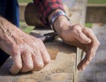 Παλαιά ανθρώπινα χέρια που στηρίζονται σε μια ξύλινη ξυλεία Στοκ Φωτογραφία