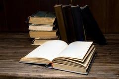 Παλαιά ανοιγμένα παλαιά βιβλία σε έναν ξύλινο πίνακα Στοκ εικόνες με δικαίωμα ελεύθερης χρήσης