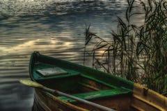 Παλαιά βάρκα με ένα κουπί στην ακτή στους καλάμους που εξισώνουν το λυκόφως Στοκ εικόνες με δικαίωμα ελεύθερης χρήσης