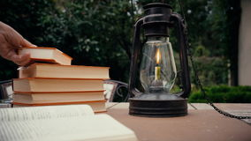 Παλαιά βιβλία λαμπτήρων και stapka κηροζίνης στον πίνακα στον κήπο το χέρι βάζει το βιβλίο στον πίνακα Φθινόπωρο απόθεμα βίντεο