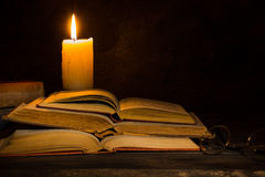Παλαιά βιβλία που διαβάζονται από το φως κεριών Στοκ Φωτογραφία