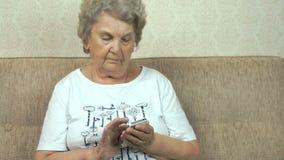 Παλαιά γιαγιά που κρατά ένα κινητό τηλέφωνο στο σπίτι φιλμ μικρού μήκους