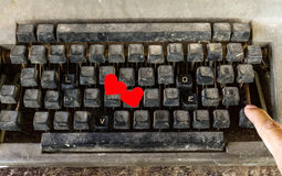 Παλαιά γραφομηχανή με τα ειδικά κουμπιά, τη λέξη ΑΓΑΠΗΣ και το χέρι του ατόμου Στοκ Φωτογραφίες