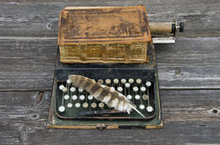 Παλαιά γραφομηχανή με την παλαιά Βίβλο βιβλίων και το φτερό πουλιών Στοκ Εικόνα