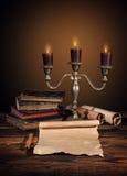 Παλαιά εκλεκτής ποιότητας βιβλία με τα κεριά στο κηροπήγιο Στοκ Φωτογραφίες