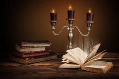 Παλαιά εκλεκτής ποιότητας βιβλία με τα κεριά στο κηροπήγιο Στοκ Φωτογραφία