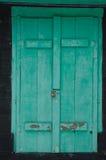 Παλαιά εξασθενισμένα πράσινα παραθυρόφυλλα που κλειδώνονται σε ένα μαύρο εξοχικό σπίτι Στοκ φωτογραφία με δικαίωμα ελεύθερης χρήσης