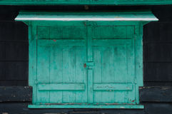 Παλαιά εξασθενισμένα πράσινα παραθυρόφυλλα που κλειδώνονται σε ένα μαύρο εξοχικό σπίτι το χειμώνα Στοκ φωτογραφίες με δικαίωμα ελεύθερης χρήσης