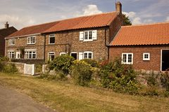 Παλαιά εξοχικά σπίτια με τα λουλούδια Colourfull. Στοκ Φωτογραφίες