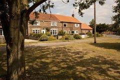 Παλαιά εξοχικά σπίτια σε ένα χωριό πράσινο. Στοκ εικόνες με δικαίωμα ελεύθερης χρήσης