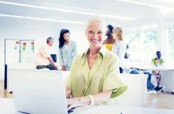 Παλαιά επιχειρηματίας που εργάζεται στο γραφείο στοκ φωτογραφία