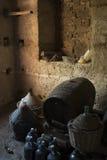 Παλαιά ηλικίας νταμιτζάνες μπουκάλια κρασιού και ξύλινα βαρέλια σε ένα υπόγειο Στοκ Φωτογραφίες