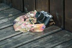 παλαιά κάμερα και ένα χαρτομάνδηλο που ξεχνιέται στον ξύλινο πάγκο Στοκ Εικόνες