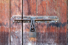 Παλαιά και αγροτική ξύλινη πόρτα με έναν σκουριασμένο σύρτη Στοκ Φωτογραφίες