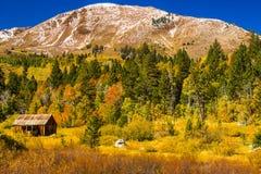 Παλαιά καμπίνα στη βάση του βουνού με τα χρώματα πτώσης στοκ εικόνες