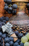 Παλαιά κανάτα κρασιού αργίλου που περιβάλλεται από τις μαύρα δέσμες σταφυλιών και το έμβλημα οινοποίησης Στοκ εικόνες με δικαίωμα ελεύθερης χρήσης