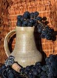 Παλαιά κανάτα κρασιού αργίλου που περιβάλλεται από τις μαύρα δέσμες σταφυλιών και το έμβλημα οινοποίησης Στοκ εικόνα με δικαίωμα ελεύθερης χρήσης