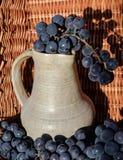 Παλαιά κανάτα κρασιού αργίλου που περιβάλλεται από τις μαύρες δέσμες σταφυλιών Στοκ Φωτογραφία