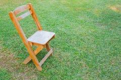 παλαιά καρέκλα στην πράσινη χλόη, αντικείμενα Στοκ Φωτογραφία