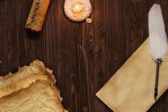 Παλαιά κενά έγγραφο και καλάμι κυλίνδρων στον ξύλινο πίνακα που φωτίζεται κοντά Στοκ εικόνα με δικαίωμα ελεύθερης χρήσης