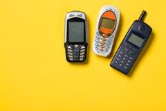 Παλαιά κινητά τηλέφωνα στο κίτρινο υπόβαθρο με ελεύθερου χώρου για το κείμενό σας Στοκ φωτογραφία με δικαίωμα ελεύθερης χρήσης