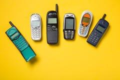 Παλαιά κινητά τηλέφωνα στο κίτρινο υπόβαθρο Στοκ Εικόνες