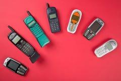 Παλαιά κινητά τηλέφωνα στο κόκκινο υπόβαθρο Στοκ Εικόνα