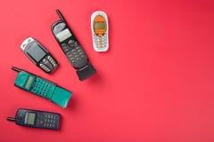 Παλαιά κινητά τηλέφωνα στο κόκκινο υπόβαθρο Στοκ φωτογραφίες με δικαίωμα ελεύθερης χρήσης