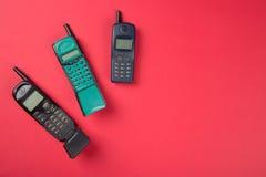 Παλαιά κινητά τηλέφωνα στο κόκκινο υπόβαθρο Στοκ Φωτογραφία