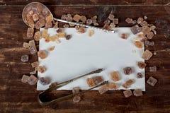 Παλαιά κουτάλια και καφετιοί κύβοι ζάχαρης με το διάστημα για το κείμενο Στοκ Εικόνες