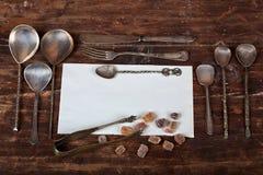 Παλαιά κουτάλια και καφετιοί κύβοι ζάχαρης με το διάστημα για το κείμενο Στοκ Φωτογραφίες