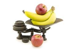 Παλαιά κλίμακα κουζινών που τίθεται με τα μήλα και τις μπανάνες Στοκ Φωτογραφίες