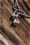 Παλαιά κλειδιά και δαχτυλίδι ενάντια στον ξύλινο τοίχο Στοκ Εικόνα