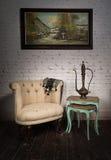 Παλαιά μπεζ πολυθρόνα, teapot ορείχαλκου, κρεμασμένη ζωγραφική και τοποθετημένοι πίνακες Στοκ Εικόνες