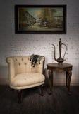 Παλαιά μπεζ πολυθρόνα, teapot ορείχαλκου, πλαισιωμένη ζωγραφική και παλαιός πίνακας Στοκ εικόνες με δικαίωμα ελεύθερης χρήσης