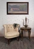 Παλαιά μπεζ πολυθρόνα, teapot ορείχαλκου, πλαισιωμένη ζωγραφική και παλαιός πίνακας Στοκ εικόνα με δικαίωμα ελεύθερης χρήσης