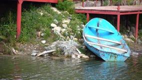 Παλαιά μπλε βάρκα κοντά στον κόκκινο πυροβολισμό αποβαθρών 4K απόθεμα βίντεο