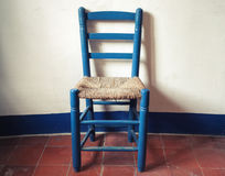 Παλαιά μπλε ξύλινη καρέκλα με το ψάθινο κάθισμα στοκ φωτογραφίες