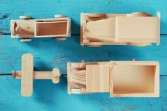 Παλαιά ξύλινα παιχνίδια μεταφορών: τραίνο, αυτοκίνητο, διαδρομή και αεροπλάνο στο μπλε ξύλινο υπόβαθρο που φιλτράρεται τρύγος και Στοκ Εικόνες