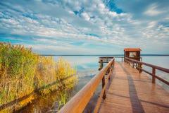 Παλαιά ξύλινη αποβάθρα για την αλιεία, το μικρό υπόστεγο σπιτιών και την όμορφη λίμνη Στοκ Φωτογραφίες
