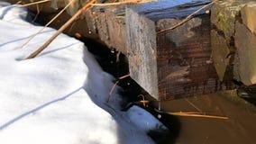 Παλαιά ξύλινη γέφυρα των κούτσουρων Χειμώνας, στάλαγμα χιονιού φιλμ μικρού μήκους