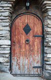 Παλαιά ξύλινη πόρτα με το λαβή-beater επεξεργασμένου σιδήρου Στοκ φωτογραφία με δικαίωμα ελεύθερης χρήσης