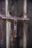 Παλαιά ξύλινη πόρτα με το παραθυρόφυλλο που στρίβεται από το καλώδιο ανασκοπήσεις που τίθεν&tau Στοκ εικόνες με δικαίωμα ελεύθερης χρήσης